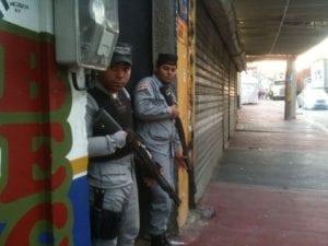Agentes se resguardan de los ataques de personas que protestan.