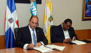 El administrador general del Banco de Reservas, Enrique Ramírez Paniagua, y el rector del Universidad Católica de Santo Domingo, Jesús Castro, firman el acuerdo de colaboración.