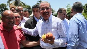 El presidente Medina con varios frutos producidos en unos de los campos visitados.