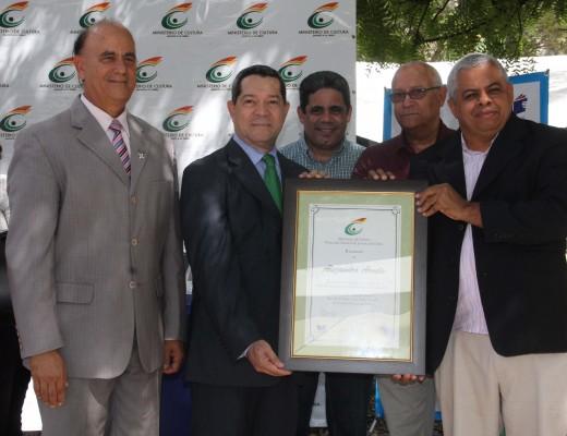El homenajeado, escritor Alejandro Arvelo, recibe el pergamino de reconocimiento.